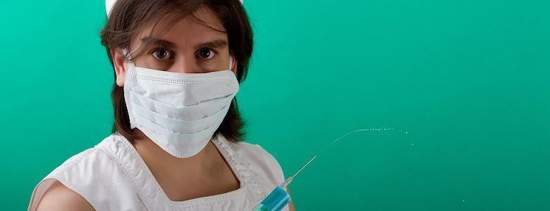 Sara mit Krankenschwester-Haeubchen und Mundschutz beim Aufziehen einer Spritze