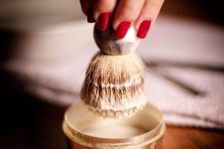 Grossaufnahme: Aufschlagen von Rasierschaum in eleganter Rasierdose mit schoenem, dicken Pinsel und mit rotlackierten Fingernaegeln