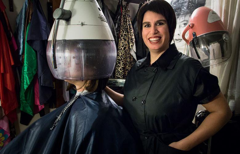 Fetischfriseuse Sara im Nylonkittel an der Trockenhaube